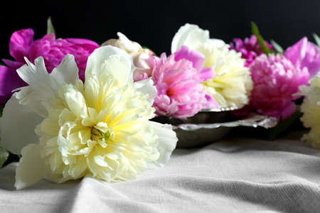 Composition with fresh peony flowers on white fabric closeup