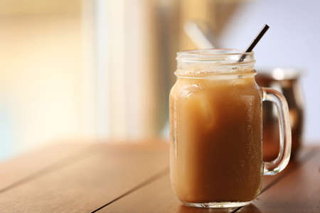Iced coffee in glass jar with straw on brown wooden table Stock Photo