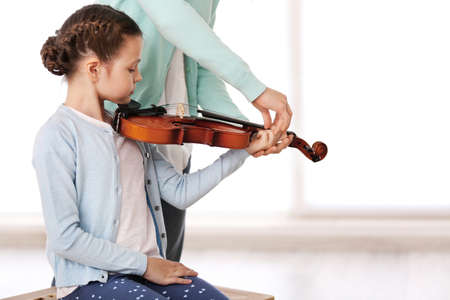 Small girl learning play violin with teacher Archivio Fotografico