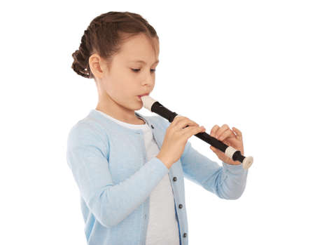 Little girl playing flute on light background 스톡 콘텐츠