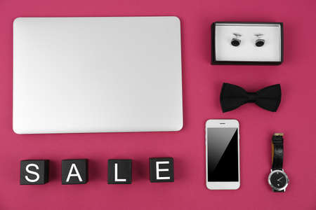 Black wooden cubes with laptop and personal stuff on color background. Sale concept