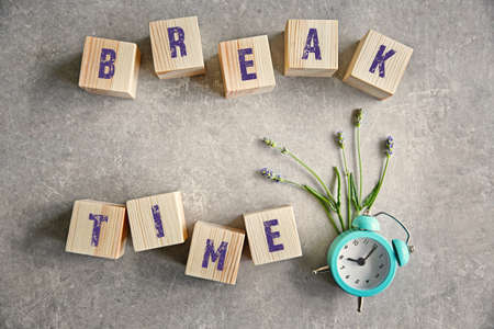 Wooden cubes with clock on a color background. Break time concept