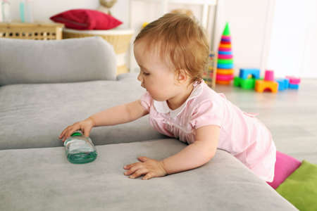 Baby with bottle on sofa in room