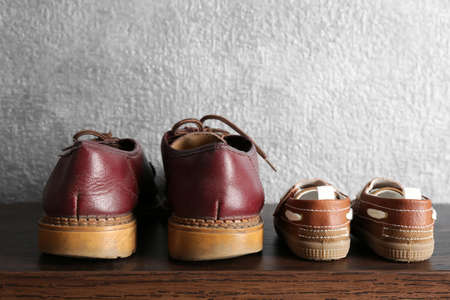 Big and small shoes on wooden table