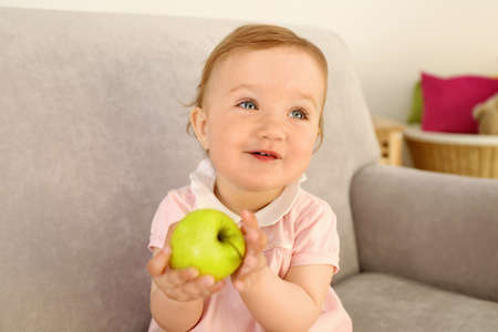 Baby with apple on sofa in room Фото со стока