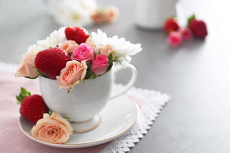 Roses and strawberries with cup on table