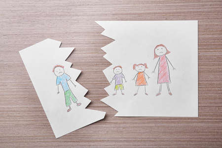 Torn drawing on wooden table. Family law concept