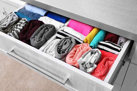 Neatly folded clothes in chest of drawers Stock Photo