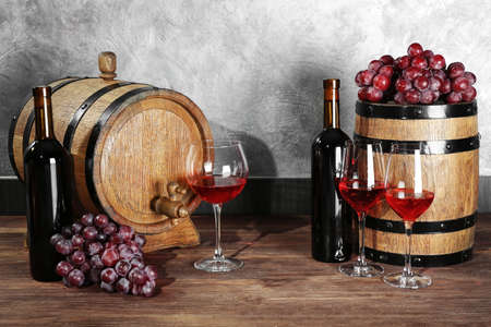 Glasses of red wine, grapes and barrels on a wooden table