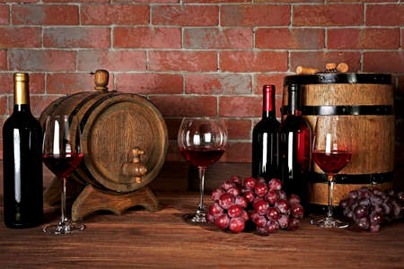 Glasses of red wine, grapes and wooden barrels on a brick wall background Banco de Imagens