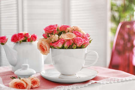 Pink roses in cup on napkin Stock Photo
