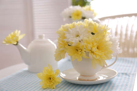 Flower bouquet of chrysanthemum in cup on blue napkin Stock Photo