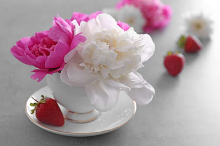 Bouquet of peonies in cup and strawberries on table