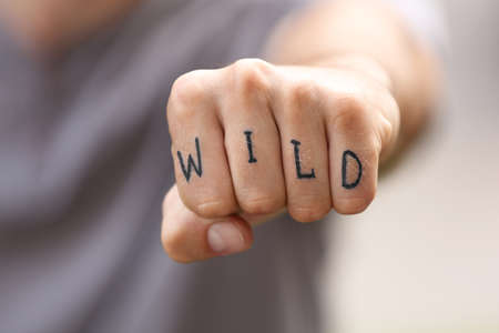Closeup oh man showing fist with fake tattoo saying WILD Stock Photo