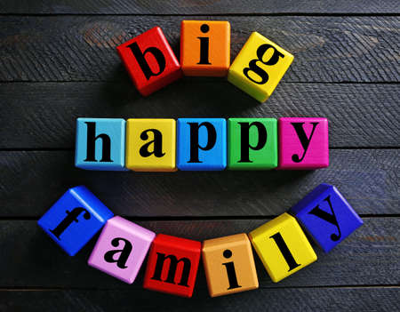 Color words BIG HAPPY FAMILY on wooden background