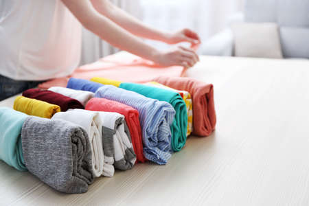 Woman folding clothes on table