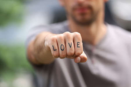 Closeup of man showing fist with fake tattoo saying LOVE