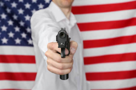 Man with gun on star and stripes background Stock Photo