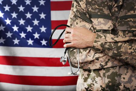 Army doctor holding stethoscope on American flag background