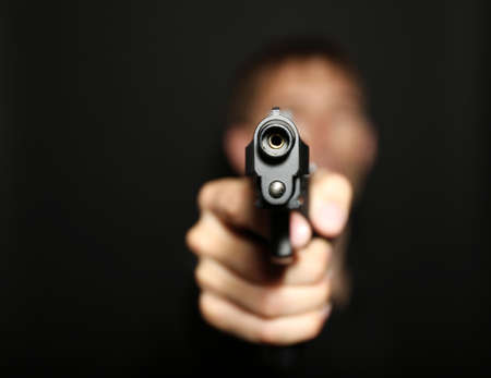 Man with gun on black background Stock Photo