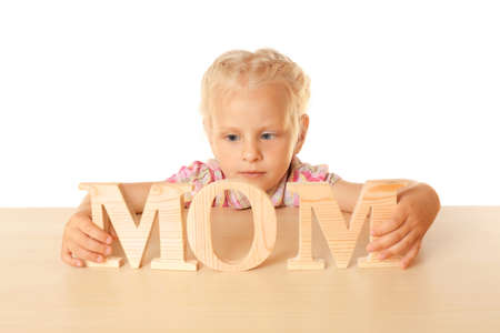 Funny little girl hiding behind table and holding wooden word MOM