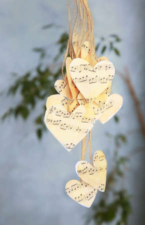 Paper hearts with music notes hanging on thread
