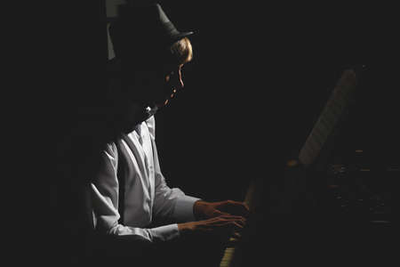 Young musician playing piano in the dark