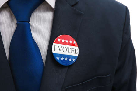 American votes concept. Voting badge  pined on coat, close up