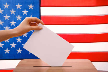 Hand putting down voting paper into a ballot box on American flag background