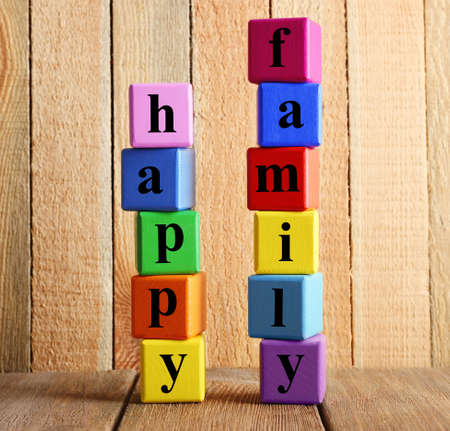 Colourful words HAPPY FAMILY on wooden background