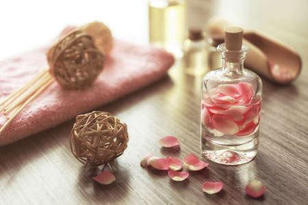 Bottle with rose petals on wooden background Standard-Bild