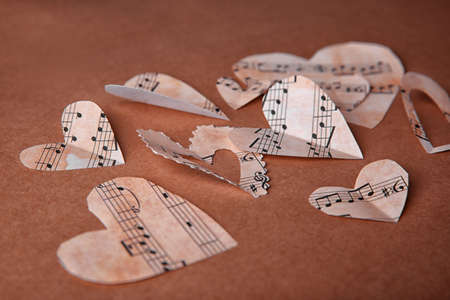 Paper hearts with music notes on brown background Stock Photo