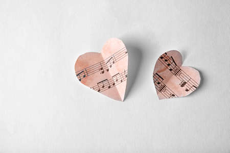 Paper hearts with music notes on white background