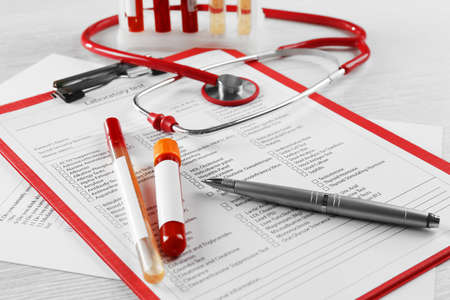 Blood samples and stethoscope on medical report 스톡 콘텐츠
