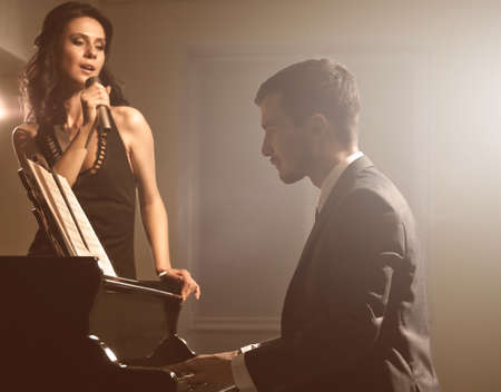 Young couple posing near piano in the dark