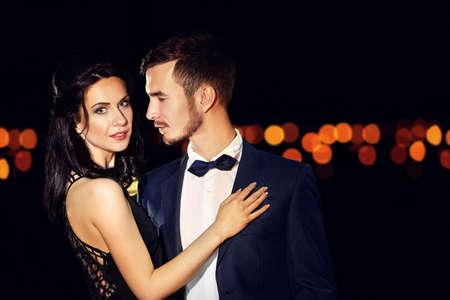 Beautiful young couple posing in the dark Фото со стока