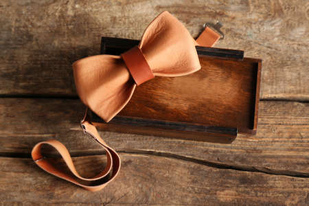 Leather bow tie and gift box on wooden background Banco de Imagens - 96041688