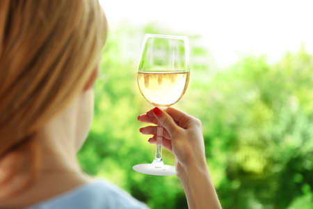 Woman holding glass of wine on blurred natural background Stock Photo