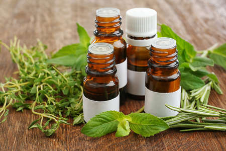 Dropper bottles and herbs on wooden background