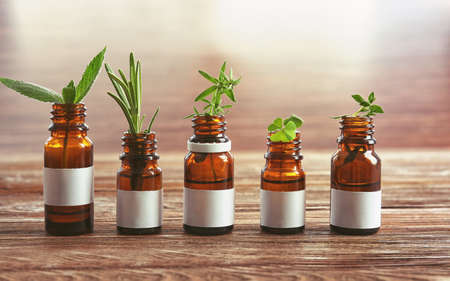 Dropper bottles and herbs on wooden table