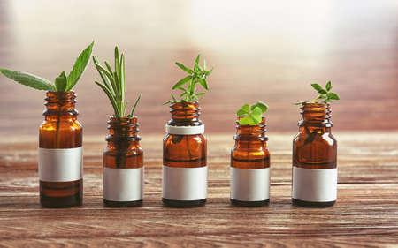 Bottiglie ed erbe del contagoccia sulla tavola di legno Archivio Fotografico