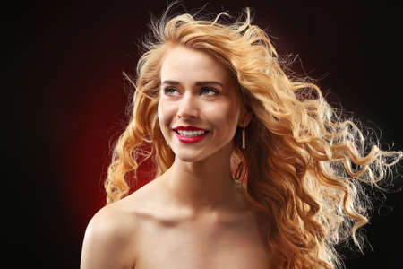 Portrait of young woman with blonde hair on dark red background Stock Photo