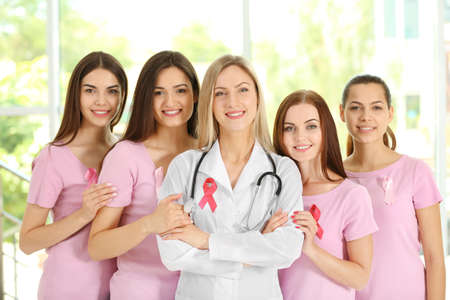 Female doctor and girls with pink ribbon. Breast cancer concept
