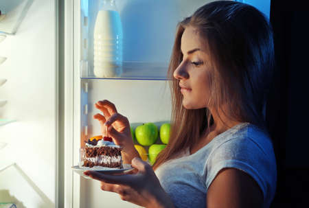 Beautiful girl eating cake at night. Unhealthy food concept