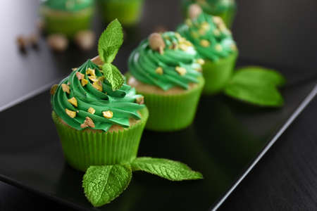 Pistachio cupcakes with mint leaves on plate Imagens