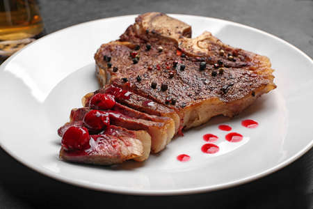 Grilled steak with drops of sauce on plate, closeup Stock Photo