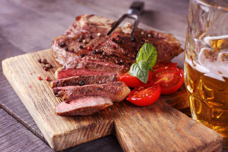 Grilled steak with tomatoes on cutting board and mug of beer, closeup