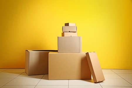House move concept. Carton boxes on yellow wall background