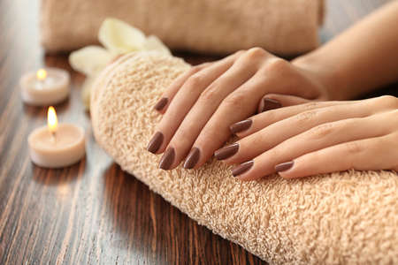 Female hands with brown manicure on towel Stock Photo