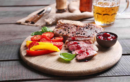 Grilled steak with fresh vegetables, sauce and beer on wooden table